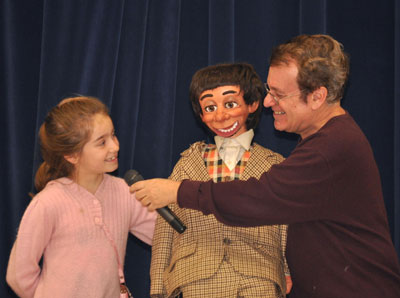 Joe Gandelman (right), ventriloquist, and one of his friends (center) offer some beginning ventriloquism lessons to a young member of their audience. Photo courtesy Joe Gandelman