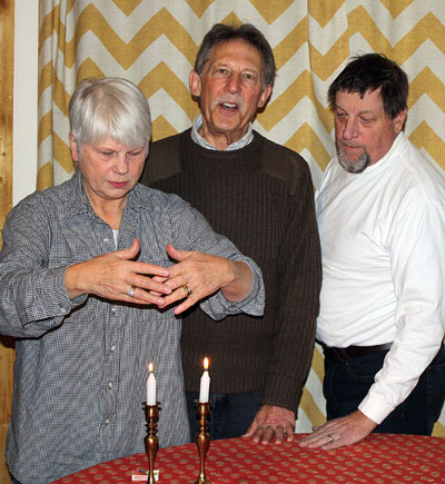 """Temple Har Shalom officers President Pat Schnetzer (left), Event Logistic Coordinator Jeffrey Cohen, (center) and Barry Zander, secretary and fundraiser, enact the lighting of the Shabbat candles. Zander pointed out that observing Shabbat is the center of Jewish observances, and the only one mentioned in the Ten Commandments, """"Remember the Sabbath Day, to keep it Holy."""" Photo by Marshall Smith"""