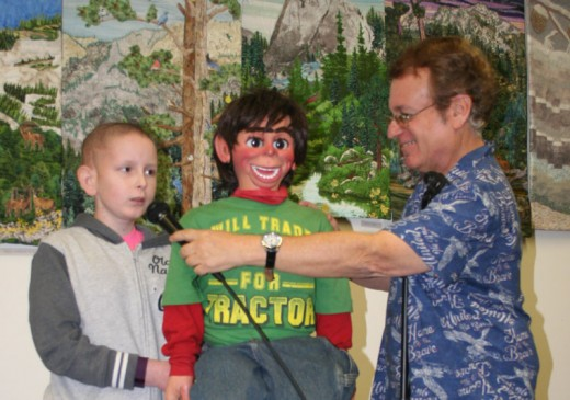 James Bachmann of Idyllwild operates ventriloquist Joe Gandelman's most difficult dummy at the Idyllwild Library Saturday. James is a burgeoning ventriloquist in his own right, and impressed Gandelman, who earlier entertained a roomful of children and adults at the free Friends of the Idyllwild Library event. Gandelman also taught the group many of his techniques. Photo by Becky Clark