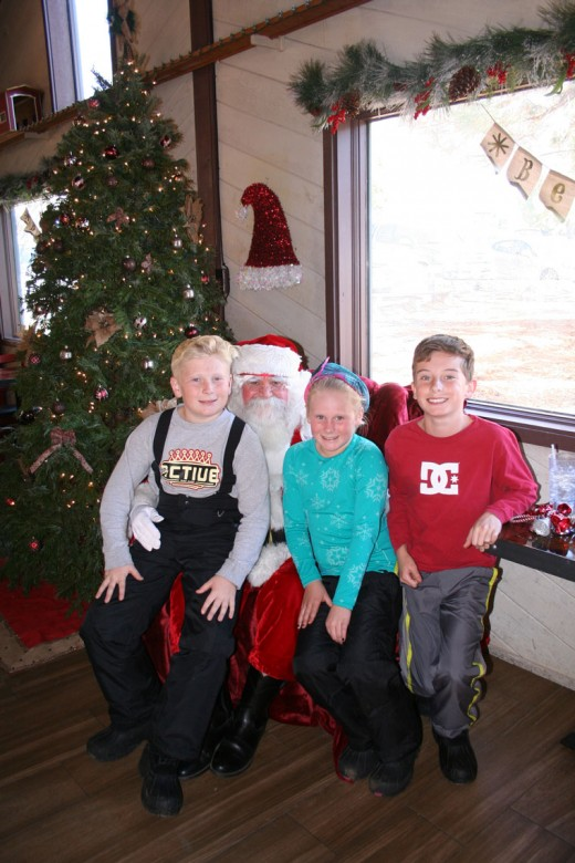 Santa Claus appeared at Jo'An's Restaurant & Bar Saturday to hear kids' Christmas wish lists and collect food for distribution to the needy. From left, Ryan Dunn, 12, Taylor Dunn, 9, and Jake Ruyle,12, all from Temecula, gather around Santa while having lunch with their families.Photo by becky Clark