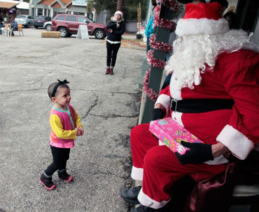 Young Lylah Potter approaches Santa for her gift at New Spirit Vacation Homes on Sunday. A representative of New Spirit Vacation Homes, which sponsored the Toy Drive, said about 90 percent of the children who received toys were from the Idyllwild area. Photo by John Drake