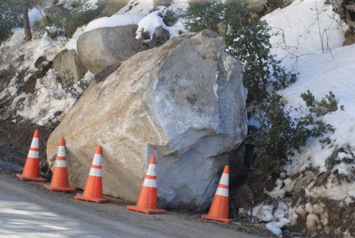 The boulder, which has been blocking Highway 243 since Sunday, is not about half its original size.