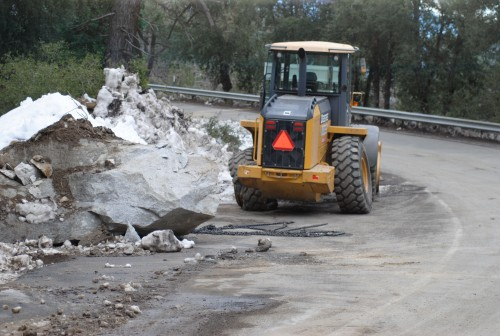 The rear wheels were damaged Tuesday when this front end loader tried to move the Hwy 243 boulder