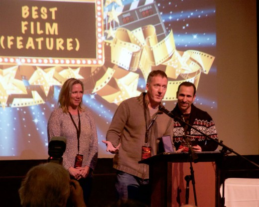 "Greg Morgan (center) accepts Best Feature award for ""The Boatman."" Morgan wrote and directed the film. He is flanked on the right by Oscar Torre who won Best Actor in a feature for his role in ""The Boatman."" Photo by John drake"