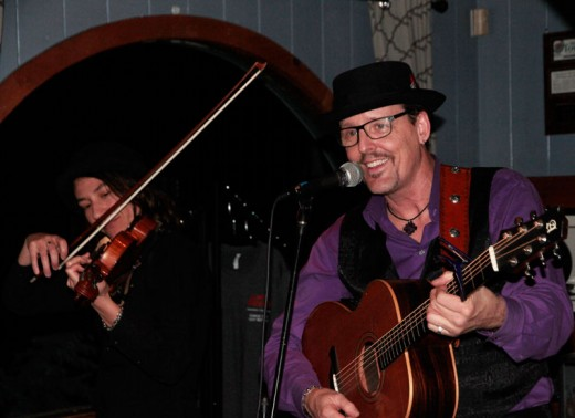 From the Netherlands, playing American folk music, Magali Michaut (left) with singing partner Brett Perkins, entertain diners at Café Aroma on Friday. They toured California with 10 shows in nine days. Photo by John Drake