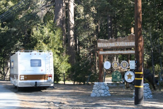 a RV is parked by the Idyllwild welcome sign. It is being lived in. A black truck, with refuse surrounding it, is parked near the RV, blocked from sight from the street by the RV. The RV had previously been parked for many months in the parking lot of a nearby building at the junction of Highway 243 and South Circle Drive. Photo by Marshall Smith
