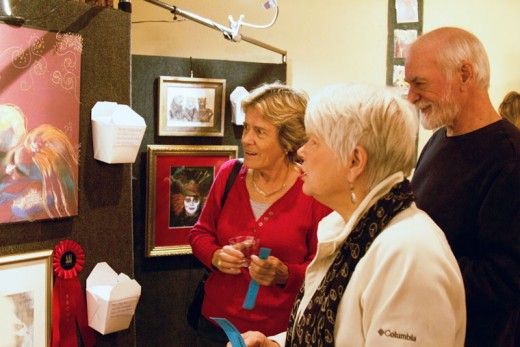 Again this year, the Art Alliance of Idyllwild's annual Eye of the Artist show attracts a large crowd to see and buy work for local artists. The crowd circled and filled the room at The Rainbow Inn for this year's AAI fundraiser (right, above). Above, Dora Dillman (from left), Pat Schnetzer and Bob Edwards study one of the award winning pieces of art at AAI's annual fundraiser Eye of the Artist. Photos by John Drake
