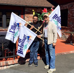 "Pete Capparelli (right), of the Idyllwild Community Center, helped install three Idyllwild Community Center ""I'M HELPING"" flags for restaurant owner Luis Solis (left), who said he is thrilled to be in Idyllwild and to have ICC flags flying in front of all three of his restaurants — Jade Mountain, Fratello's and The Lumber Mill. Photo courtesy Chris Trout"