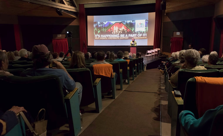 A packed Rustic Theatre listens to Chris Trout, who opened the public meeting about the Idyllwild Community Center project earlier this year. Photo by Tom Kluzak