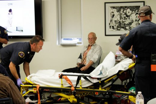 """Mountain Disaster Preparedness President Mike Feyder  being treated by Idyllwild Fire Department's Jim LaMonte (left) and Capt. Alan Lott (right) after displaying """"symptoms"""" of a heart attack. The ruse was part of an MDP talk at the Idyllwild Library on the same subject Tuesday, April 19. Photo by John Drake"""