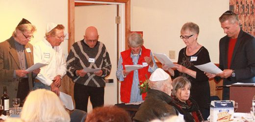 Readers tell the story of the Jews' exodus from Egypt, one of the highlights of the Community Seder Dinner held annually by Temple Har Shalom in Idyllwild. Leading the evening's observance held at the Rainbow Inn is Rabbi Jules King (right).  Congregation President Pat Schnetzer announced that the congregation now holds regular services at St. Hugh's Episcopal Church. Photo by Barry Zander