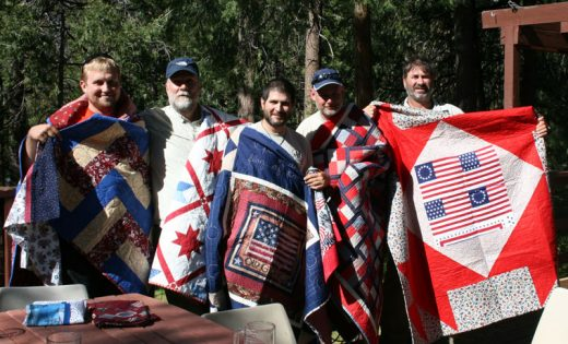 "Five military veterans are hiking the Pacific Crest Trail and stopped at the American Legion Post 800 for a reception and dinner. Four are part of ""Warrior Hike: Walk off the War"" and the fifth had been hiking solo but joined the group in Julian. Chris Finney presented quilts made by Mountain Quilters of Idyllwild to the five — from left, dubbed the ""tag along,"" Joe Thompson, U.S. Marines; Dan Janes, Navy; Ruben Munoz, Navy; Joe Jamison, Army; and Jimmy Sellers, Army. This is the third year PCT Warrior Hikers have come through Idyllwild to the legion event. Photo by Marshall Smith"