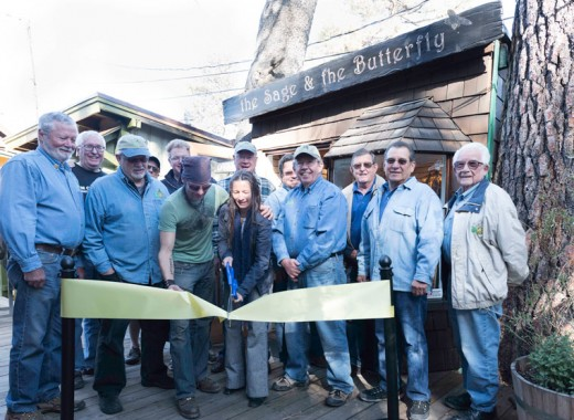 The Sage and the Butterfly, the new shop in The Village Lane, was welcomed to Idyllwild with a ribbon cutting the Idyllwild Rotary Club held Monday, April 4. The shop features handcrafted jewelry, accessories, knives and razors by local, national, international and Amazon rainforest artisans. Attending the ribbon cutting were (from left) Thom Wallace, Scott Fisher, Terry Kurr, Chuck Streeter, Chris Scott, The Sage and the Butterfly owners Violeta Vallacorta and Dylan Farnham, Chuck Streeter, John Graham, Dennis Dunbar, Rick Foster, Steve Espinoza and Earl Parker. Photo by Tom Kluzak