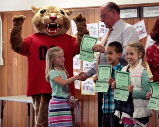 "Abigail White is presented a Six Flags Park certificate by Idyllwild School Principal Matt Kraemer and ""Rocky"" along with classmates Tyler Sonnier and McKenna Lovett for perfect attendance. Photo by John Drake"