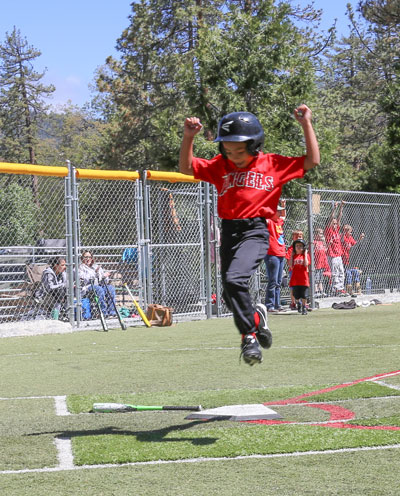 During the Town Hall Minors baseball game Saturday, this runner was very happy to score a run. Photo by Cheryl Basye