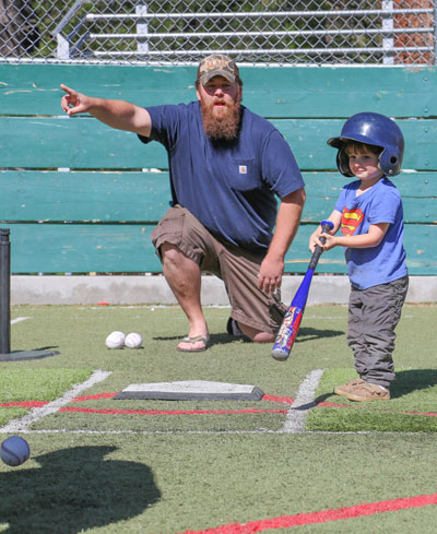 Coach Paul White helps this batter during Saturday's T-ball game.Photo by Cheryl Basye