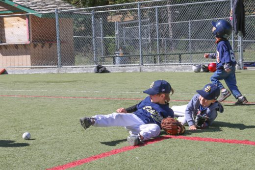 Two Padres chase down the ground ball while the Tigers' batter heads to first during Saturday's T-ball game. Photo by Cheryl Basye
