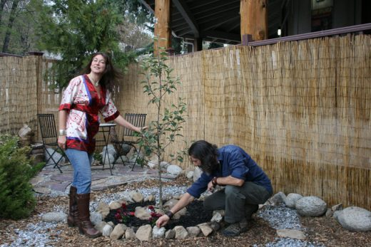 "Tricia Pilkington and Todd Fowler are seen here with the Pete ""Pedro"" Anderson memorial apple tree they planted, part of The Orchard Project, designed to plant 100 nut and fruit bearing trees in Idyllwild public areas over the next ten years – 10 trees per year.Photo by Marshall Smith"
