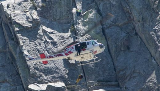 A male climber was rescued from Lily Rock Sunday afternoon, May 22, after complaining of chest pain while rock climbing. The patient was able to belay down to solid ground where firefighters assisted him, preparing him to be hoisted into Helicopter 301. Here one of the helicopter crew descends to help prepare the climber to be hoisted up and transported for further medical aid. Rock climbers unrelated to the incident can be seen in the background just above the helicopter. At the ambulance, the patient refused transport to a medical center.Photo by Jenny Kirchner