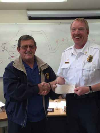 Rick Foster presents a $1,000 check from the Idyllwild Rotary to Idyllwild Fire Chief Patrick Reitz. The money will go toward the bathroom renovation at the Idyllwild station. Photo courtesy Chuck Weisbart