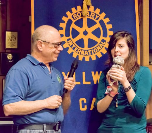"""Novelist, speaker and freelance editor Kara Swanson (right) receives a coveted Idyllwild Rotary squirrel from Rotary President Chuck Weisbart at the weekly Rotary meeting on May 4. Kara spoke about her experiences growing up in Papua New Guinea and the intricacies of writing and self-publishing a novel, """"Pearl of Merlydia,"""" with friend Charis Smith. Kara's goal as an already-accomplished 19-year-old writer is to use """"words that bring worlds to life.""""Photo by Tom Kluzak"""