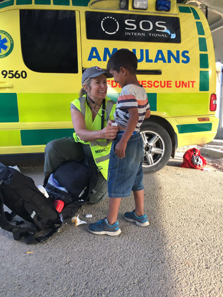 Mary Lehman, local attorney, serving as an EMT at a refugee camp in northern Greece is seen here examining a young resident of the camp. Later, a number of the young boys, with whom Lehman had interacted and tried out her Arabic, donned yellow volunteer vests, and with borrowed stethoscopes, paraded around laughing and mimicking Lehman's Arabic. Photo courtesy of Mary Lehman