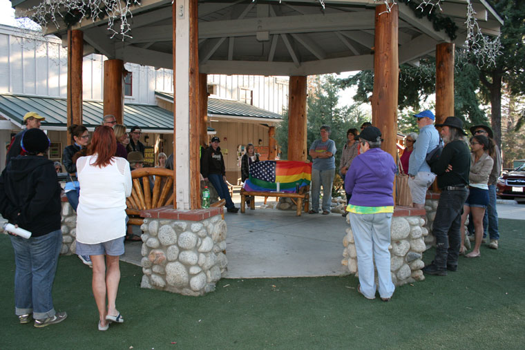 """About 40 people attended a vigil in Idyllwild Monday evening, June 13, to honor the dead from the mass fatal shooting in Orlando. The attack in Florida, the largest mass shooting in U.S. history, took place at a club frequented primarily by LGBT adults. In this photo, a U.S. rainbow flag is the centerpiece emblem of inclusion. The United States is now one of many countries where gay marriage is legal and LGBT rights are protected. Even so, attendee and Idyllwild resident Eduardo Santiago said, """"Even now I don't feel safe. Someone at the next restaurant table could overhear my conversation and make an ugly scene.""""Photo by Marshall Smith"""