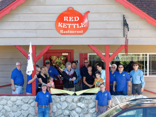 The Idyllwild Rotary Club officiated at the ribbon cutting of the Red Kettle on June 6, welcoming new owner Bruce Ross. Those present for the ceremony included: (on deck from left) Scott Fisher, Terry Kurr, Jamie Ludy with daughter Mickayla, Lindsay Kringle-Owen, Thom Wallace, Bruce Ross with scissors, John Graham, Roger Reeder, Kim Crandall, Annie Weaver with grandson Carter, Earl Parker, Steve Espinosa, and Jeffrey Cohen. On sidewalk (from left) are Chuck Streeter, Roland Gaebert.Photo by Tom Kluzak