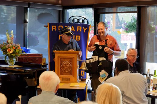 "Outgoing president and pilot Chuck Weisbart (left) passes duties on to new president and captain of the ship Marc Kassouf (right) at the Idyllwild Rotary's annual Out 'n' In Dinner Wednesday, June 15. Members and guests filled the Mile High Café as Kassouf was presented with a personalized life vest to help him with the ""sink or swim"" orientation to his new position leading the Idyllwild Rotary Club. Photo by Tom Kluzak"