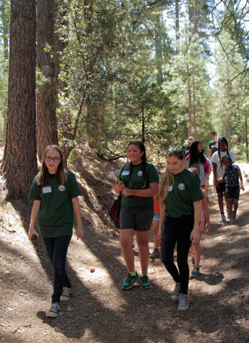 Junior Naturalists (from left) Cecile Laundré, Jessica Ruelas and Rory Wilke were among five who took visitors to the Nature Center on a walk to see historical features of the mountain last Saturday.Photo by John Drake