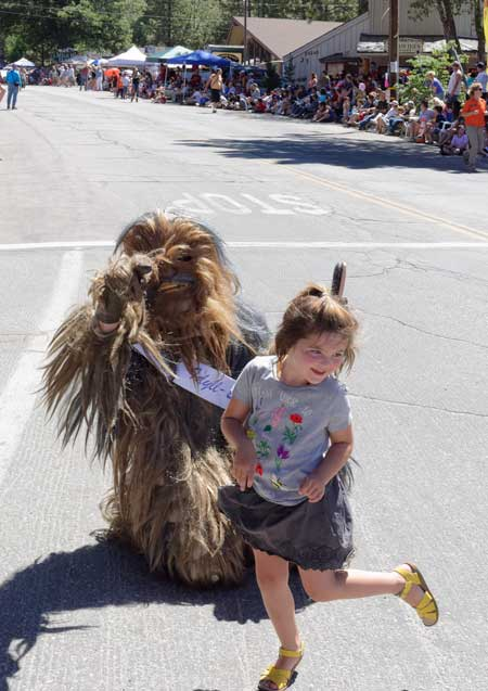 The Idyll Beast dances with one of the parade's spectators.Photo by Tom Kluzak