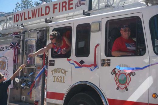 Rachel Teeguarden distributes flags from the Idyllwild Fire Department's ladder truck and Jerry Buchanan, president of the Idyllwild Fire Protection District commission, enjoys the ride. Photo by Chandra Levy