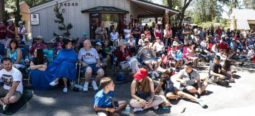 A very large crowd enjoys the 2016 Fourth of July Parade from near the corner of Village Center and North Circle drives.Photo by Peter Szabadi