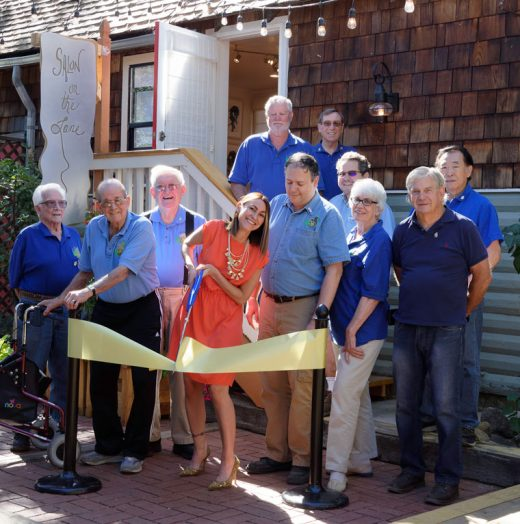 Franceska Schofield, owner of the newly opened Salon on the Lane at the end of Village Lane, performs the ceremonial cutting of the ribbon welcoming her business to Idyllwild. Those in attendance were, from left, Rotarians Earl Parker, Charlie Wix, Bob Parish, Schofield, Thom Wallace, Marc Kassouf, Roland Gaebert, John Graham, Reba Coulter, Jeff Campbell and Ted Kinoshita. The salon offers haircuts for men and women as well as coloring and facial waxing.  Photo by Tom Kluzak