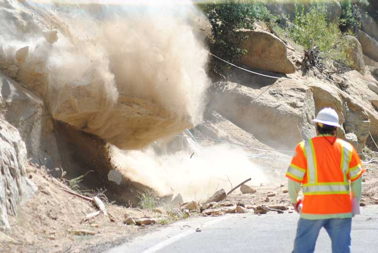 One of two boulders above Highway 243 at Deadman's Curve in Pine Cove is pulled off the steep slope on Wednesday morning. A Caltrans team is removing these so they do not fall unexpectedly on the highway, as one did last January. The crew used air bags to push the second boulder onto the highway.Photo by JP Crumrine