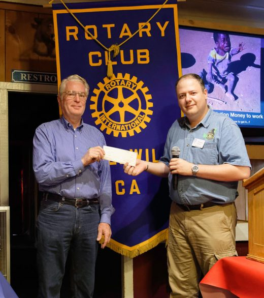 Idyllwild Rotary President Marc Kassouf presents a check for $1,000 to Ken Dahleen to help support the Idyllwild Summer Concerts. The series, a highlight of summer in Idyllwild, is a very expensive undertaking that depends on community support. The U.S. Marine Surprise Band, appearing on July 28, is made up of retired Marine Band members from around the country, assembled at Dahleen's request because of the community interest. when none of the active Marine Bands were available.