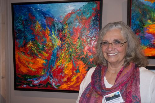 "Jacque Swerdfeger stands in front of her art work during the ""Art Uncorked — Afternoon with the Artist"" show at Middle Ridge Winery Tasting Gallery on Saturday. Photo by Peter Szabadi"