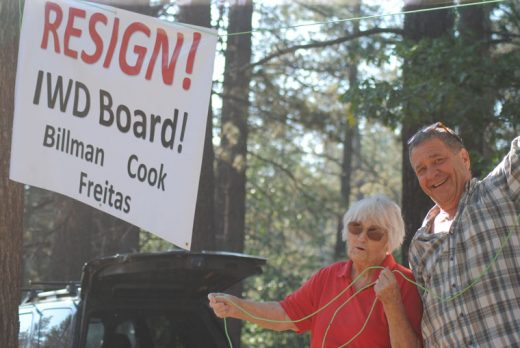 "Last week, several citizens elevated their concerns about the Idyllwild Water District directors' actions. Here, Marge Muir and Vic Sirkin help raise a ""Resign"" sign. Four other signs were posted throughout Idyllwild; however, one was removed Saturday night.    Photo by JP Crumrine"
