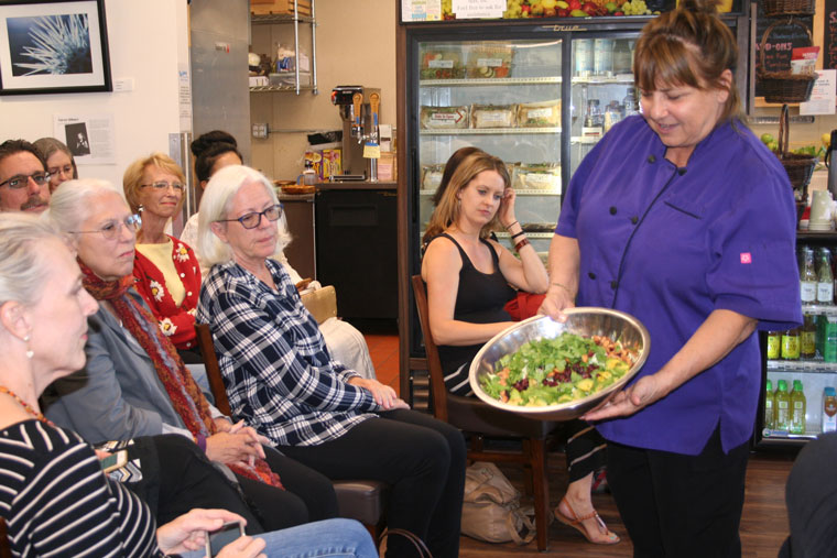Chef Tanya Petrovna, founder of the Native Foods Café in Palm Springs, shows a large crowd a healthful, completely plant-based salad before making the dressing at a demonstration at Sky Island Organics Monday night. Photo by becky clark