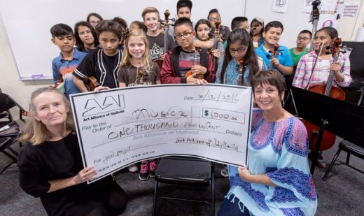 "Anna Ancheta (left), director of Musica!, and Teresa DiPietro, head teacher/conductor of Musica! Echorchestra, accept a donation from the Art Alliance of Idyllwild. The $1,000 grant will be used to fund ""Pictures at an Exhibition"" that combines student and professional art along with music.  Photo by Peter Szabadi"
