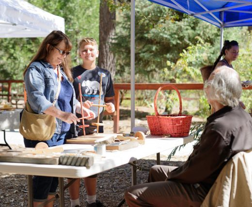 "Sandy Ezell (left) of Idyllwild and grandson Robert Martinez of Hemet work at drilling holes using tools similar to those the Cahuilla people used when they occupied the site of the Idyllwild Nature Center. The center hosted the annual ""Trail of the Acorn"" event. George Ray (right) provided the equipment and instruction as part of the demonstration, which offered a look at the life of the nomads as they followed the plants that were in season between the desert and mountains. Photo by Tom Kluzak"