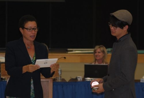 Dr. LaFaye Platter (left), deputy superintendent at Hemet Unified School District, read the recognition for Nam Park, who was the recipient of the district's Good Apple Award for her volunteer service at Idyllwild School. Park could not attend the HUSD Oct. 4 board meeting at Idyllwild School, and her son, Jason, accepted the award on her behalf.   Photo by JP Crumrine