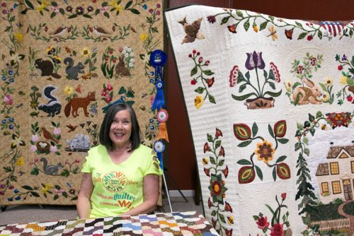 Billy Kercmer poses with her quilts. She was the featured quilter at the annual Mountain Quilters of Idyllwild Quilt Show on display at Buckhorn Camp over the weekend. Photo by Jenny Kirchner