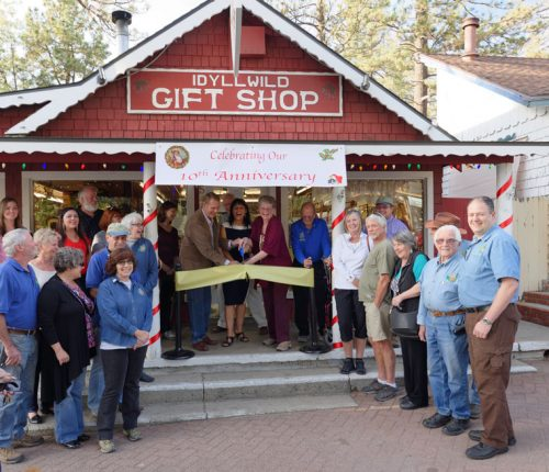 Friends of the Idyllwild Gift Shop and members of the Idyllwild Rotary Club helped the shop owners celebrate their 10th anniversary on Friday, Oct. 7, with a ribbon cutting. Attempting to cut the uncooperative ribbon are owners Rick Shahan (from left) with wife Colleen and mother Judy Begin.Photo by Tom Kluzak