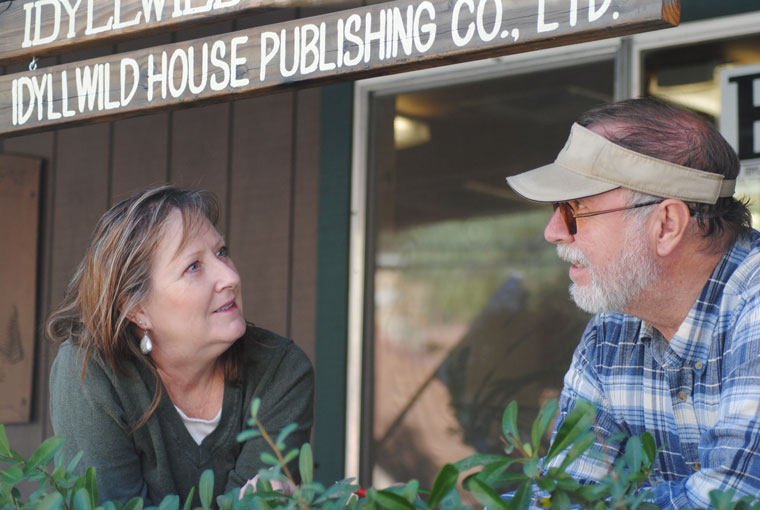 Becky and Jack Clark, co-owners and publishers of the Idyllwild Town Crier, celebrate the 70th anniversary of the paper's founding in 1946. The first edition came out on Nov. 1, 1946. The Clarks are on the porch of the Town Crier's sixth location in its 70 years of publication.Photo by Marshall Smith