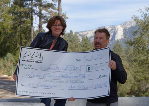 Shanna Robb, Art Alliance of Idyllwild president, presents a check for $11,000 to Michael Slocum, Associates of the Idyllwild Arts Foundation president, on the campus of Idyllwild Arts. The donation represents a portion of the proceeds from the 19th annual Art Walk and Wine Tasting in October and will be used for scholarships for campus students.   Photo by Tom Kluzak