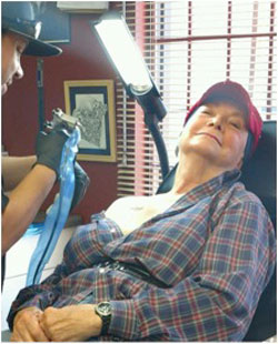 Judy Lawler of Idyllwild, relishing her first experience at a tattoo parlor, takes pleasure in sending cancer a message of defiance last Saturday.    Photo by Lori Cornell