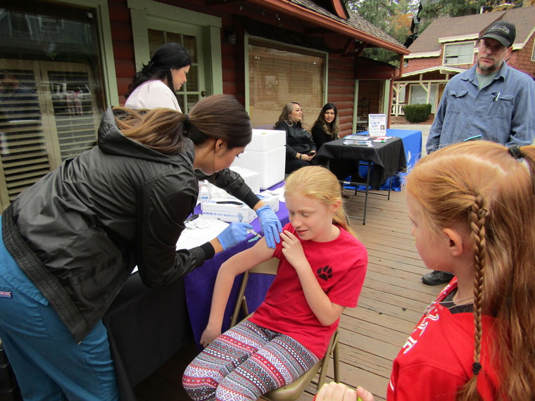 The Idyllwild HELP Center's annual Health Fair was at Fern Creek Medical Center Saturday, Nov. 12. Flu shots are one of the popular features. Here, Lyliann Johnston is getting vaccinated while her father Casey and sister Kaelynn watch. Photo by Amy Righetti