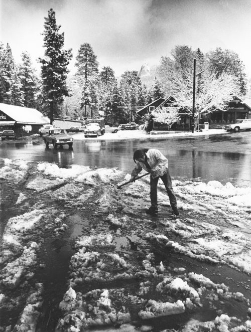 Dan Gallagher shovels to clear the drive in front of Osuna's Chevron station as the cloud level lifts above Lily Rock in November 1973. File photo/Norwood Hazard