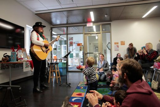 Sandii Castleberry plays holiday songs for parents and kids during Storytime at the Idyllwild Library Monday morning. Photo by John Drake